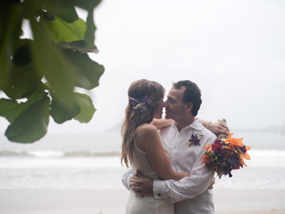 Groom holding his bride after their elopement in Tamarindo, Costa Rica. Photographed by Kristen M. Brown, Samba to the Sea Photography.
