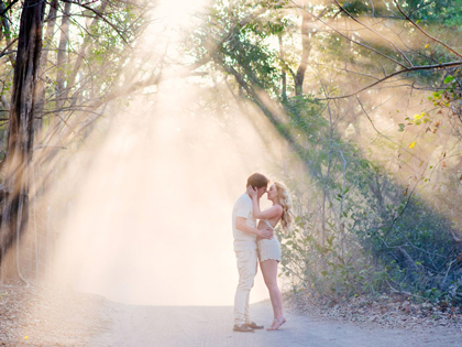 Couple romantically kissing as the sun streams through the trees in Playa Conchal, Costa Rica. Photographed by Kristen M. Brown, Samba to the Sea Photography.