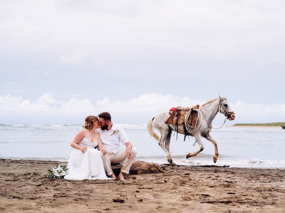 White horse running behind bride and groom kissing on the beach in Costa Rica.