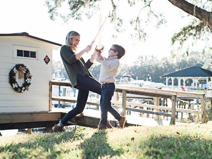 Mom and young son sword fighting during family photos on Bluff Drive in Isle of Hope, GA. Photographed by Kristen M. Brown, Samba to the Sea Photography.