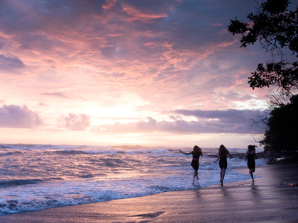 Cousins running on the beach during a stunning sunset in Costa Rica. Photographed by Kristen M. Brown, Samba to the Sea Photography.