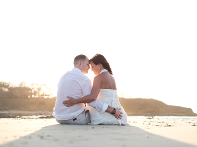 Bride and groom sitting on the beach after their elopement in Tamarindo, Costa Rica. Photographed by Kristen M. Brown, Samba to the Sea Photography.