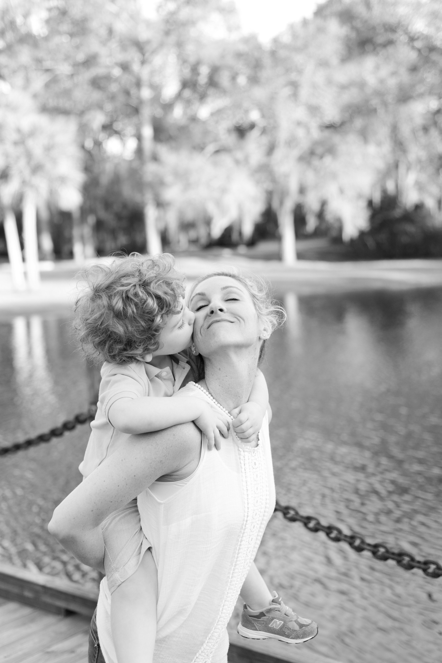 Young boy kissing his mother on the cheek at The Landings on Skidaway Island in Savannah, GA. Photographed by Savannah Family Photographer Kristen M. Brown, Samba to the Sea Photography.
