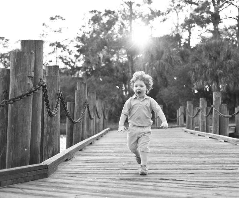 Black and white photo of young boy running on wood bridge at The Landings in Savannah, Georgia. Photographed by Savannah Family Photographer Kristen M. Brown, Samba to the Sea Photography.