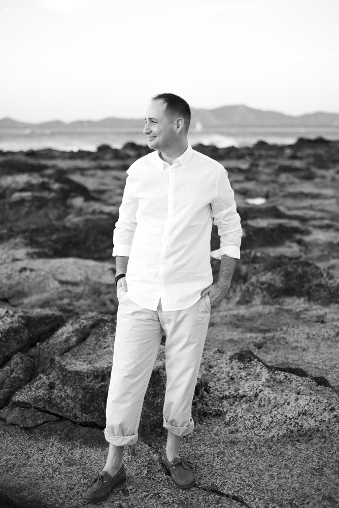 Black and white photo of groom on the low tide rocks in Tamarindo, Costa Rica. Photographed by Kristen M. Brown, Samba to the Sea Photography.