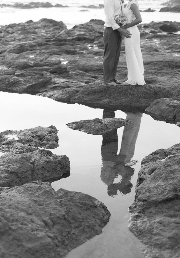 Bride and groom kissing reflection in a low tide pool in Playa Langosta, Costa Rica