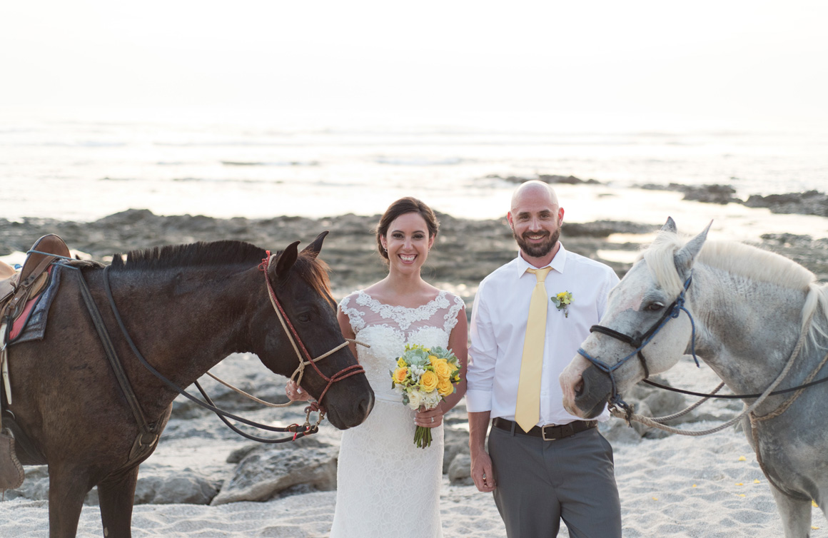 Bride and groom holding horse leads during Wedding in Playa Langosta, Costa Rica