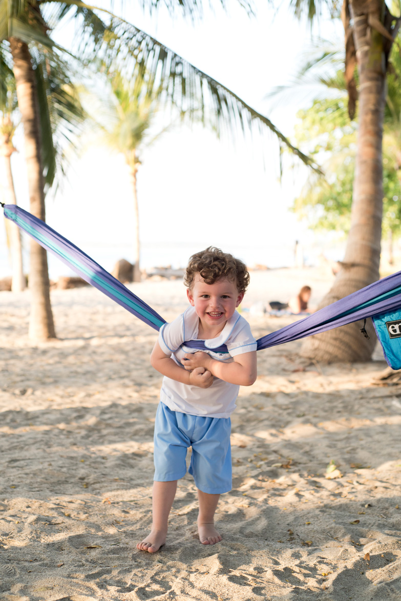 Boy with hammock on the beach in Tamarindo, Costa Rica. Photographed by Kristen M. Brown, Samba to the Sea Photography.