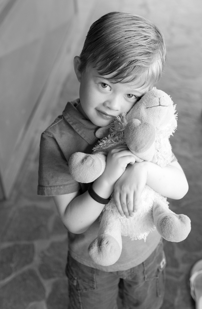 Young boy holding his stuffed animal at Casa Redonda in Tamarindo, Costa Rica. Photographed by Kristen M. Brown, Samba to the Sea Photography.