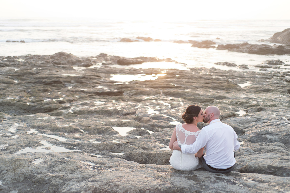 Bride and groom kissing on the low tide rocks in Playa Langosta, Costa Rica