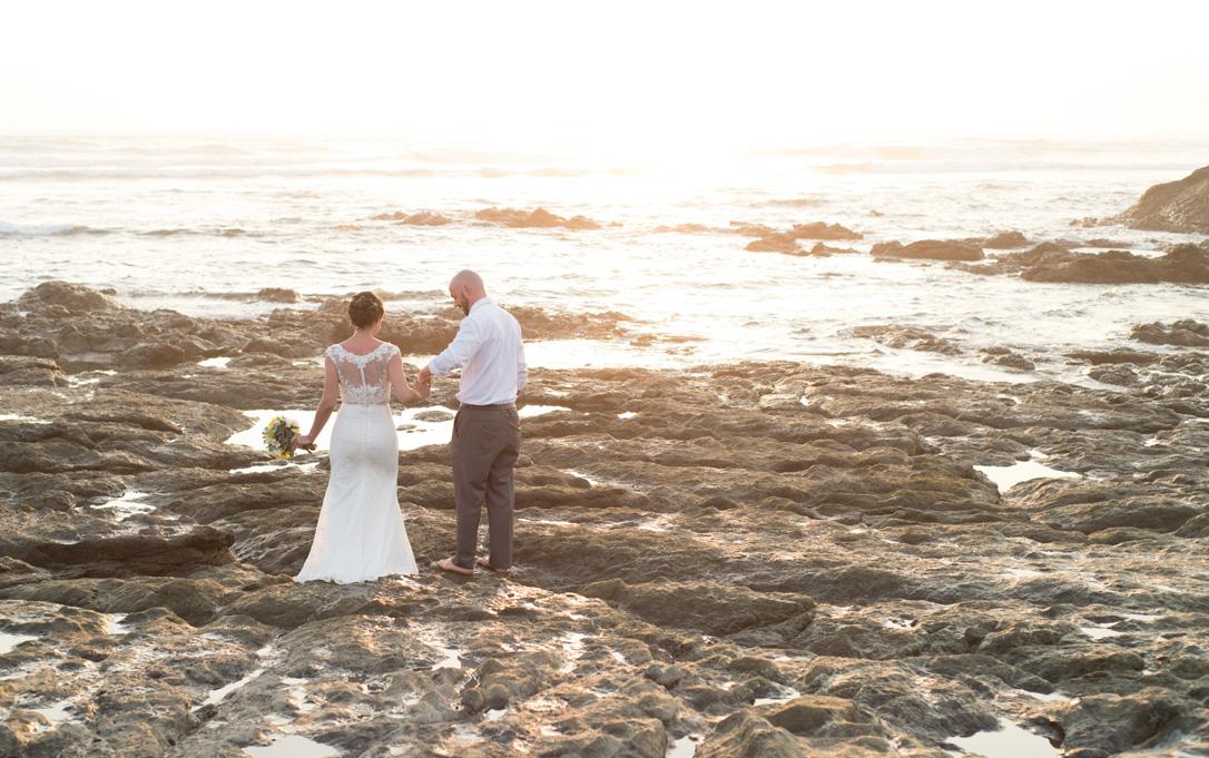Bride and groom walking on the low tide rocks in Playa Langosta, Costa Rica