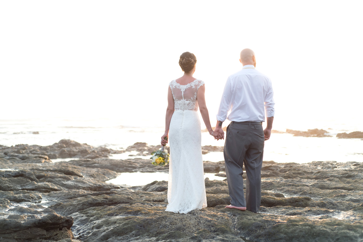 Bride and groom looking at ocean on Playa Langosta, Costa Rica