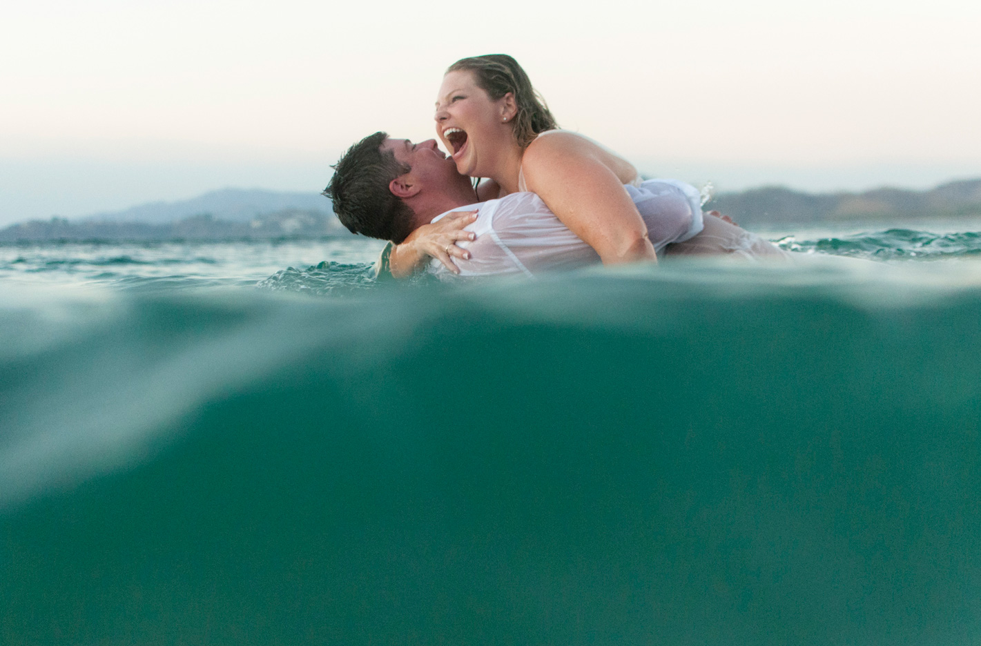 Bride and groom laughing in the ocean during trash the dress photos in Playa Conchal, Costa Rica. Photographed by Kristen M. Brown, Samba to the Sea Photography.