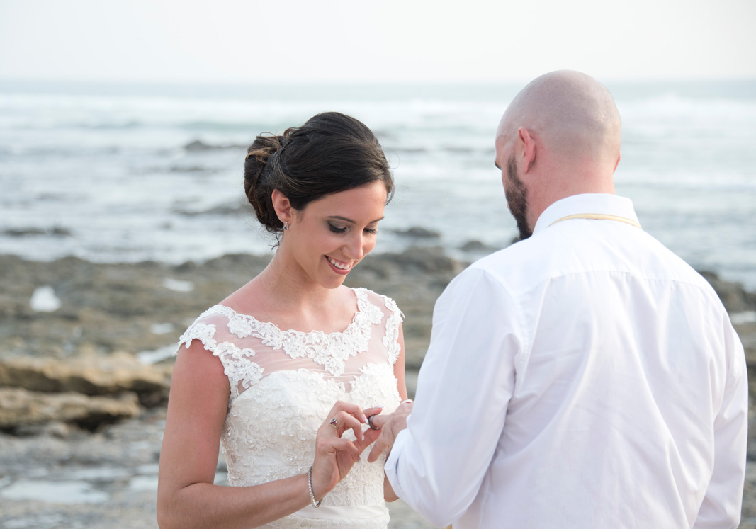 Bride putting ring on groom during Elopement in Playa Langosta, Costa Rica