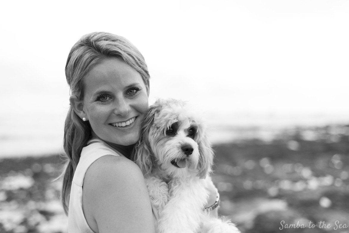 Black and white photo of Waffles the Cavapoo and Theresa in Tamarindo Beach, Costa Rica. Photographed by Kristen M. Brown, Samba to the Sea Photography.