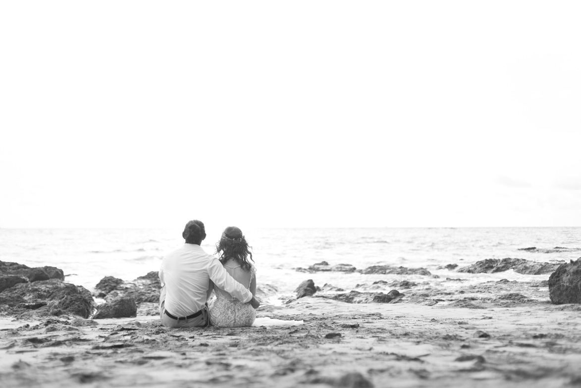Black and white photo of bride and groom sitting on the beach in Playa Hermosa, Costa Rica. Bride and groom standing on the low tide rocks at Playa Hermosa, Costa Rica. Photographed by Kristen M. Brown, Samba to the Sea Photography.