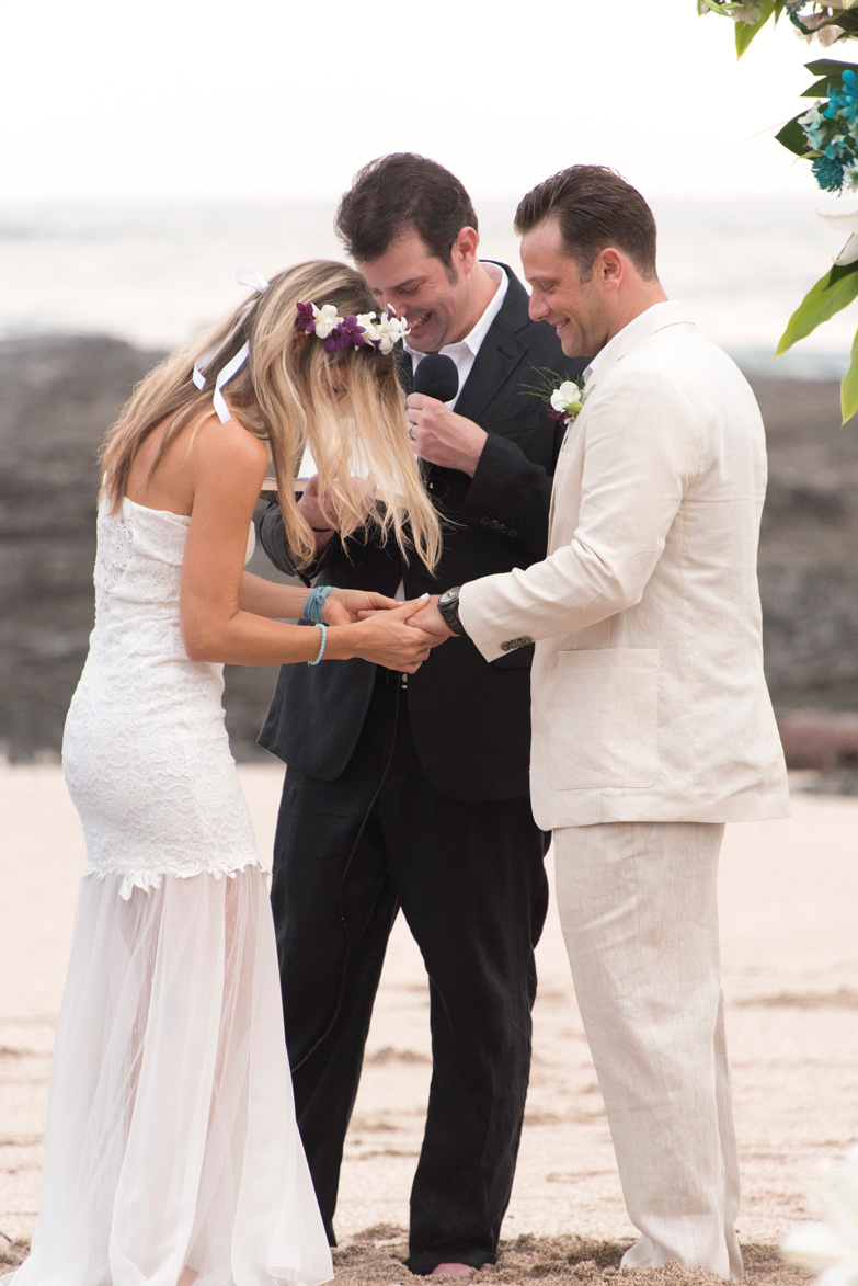 Bride putting on groom's wedding ring at beach wedding on Playa Langosta, Costa Rica. Photographed by Kristen M. Brown, Samba to the Sea Photography.