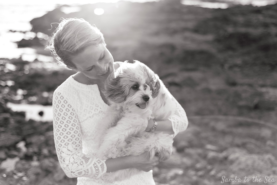 Black and white photo of Waffles the Cavapoo and Theresa in Tamarindo, Costa Rica. Theresa is wearing the Lilly Pulitzer Mara Scallop Hem Lace Dress. Photographed by Kristen M. Brown, Samba to the Sea Photography.