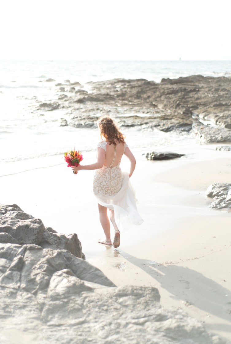 Bride walking to the ocean on Playa Hermosa, Costa Rica. Photographed by Kristen M. Brown, Samba to the Sea Photography.