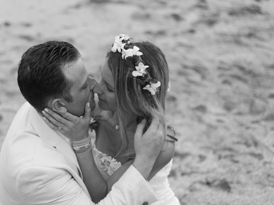 Black and white photo of bride and groom kissing on the beach in Playa Langosta, Costa Rica. Photographed by Kristen M. Brown, Samba to the Sea Photography.