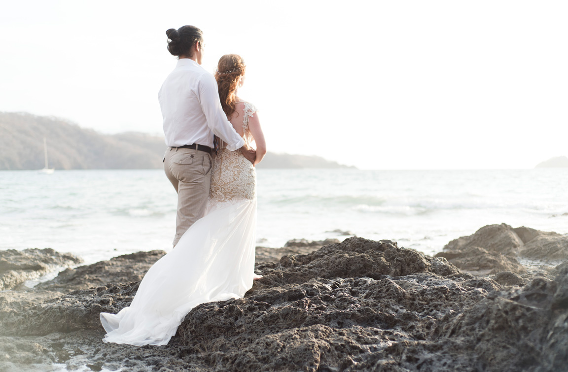 Bride and groom standing on the low tide rocks at Playa Hermosa, Costa Rica. Photographed by Kristen M. Brown, Samba to the Sea Photography.