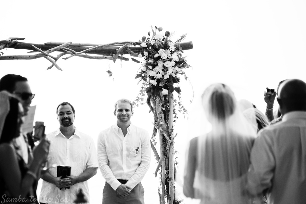 Groom smiling at his bride as she walks down the aisle during their Langosta Beach Club wedding. Photographed by Kristen M. Brown, Samba to the Sea Photography.