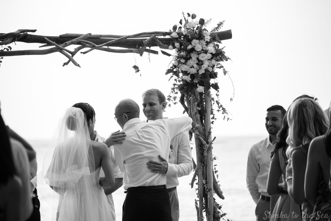 Groom hugging brides father during his Langosta Beach Club wedding. Photographed by Kristen M. Brown, Samba to the Sea Photography.