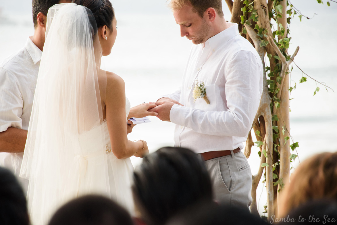 Groom putting on bride's wedding ring during their Langosta Beach Club wedding in Tamarindo, Costa Rica. Photographed by Kristen M. Brown, Samba to the Sea Photography.
