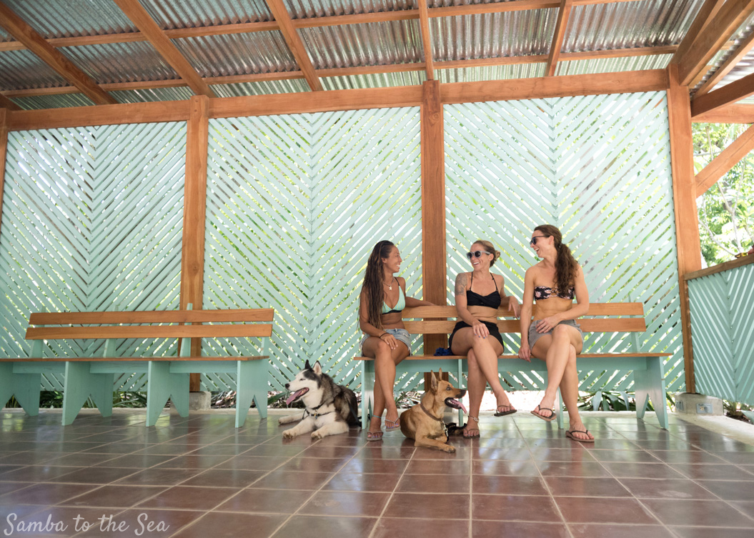 Women and their dogs at the Harmony Hotel in Nosara, Costa Rica. Photographed by Kristen M. Brown, Samba to the Sea Photography.