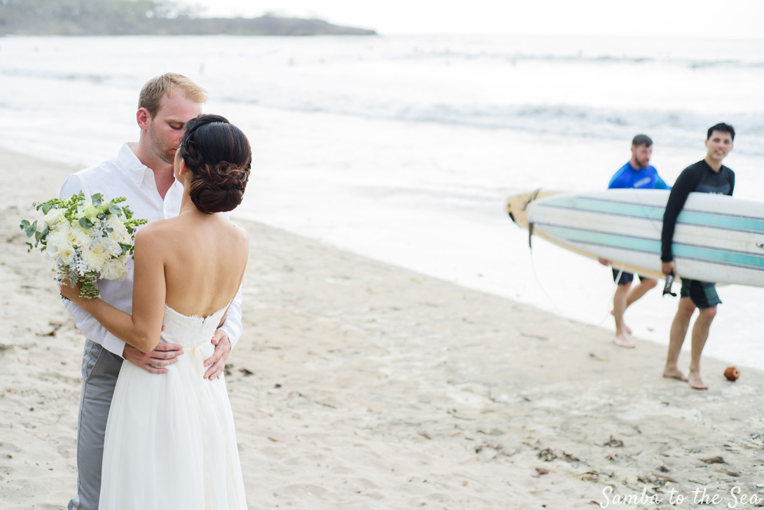 Surfers passing behind bride and groom kissing after their wedding in Tamarindo, Costa Rica. Photographed by Kristen M. Brown, Samba to the Sea Photography.