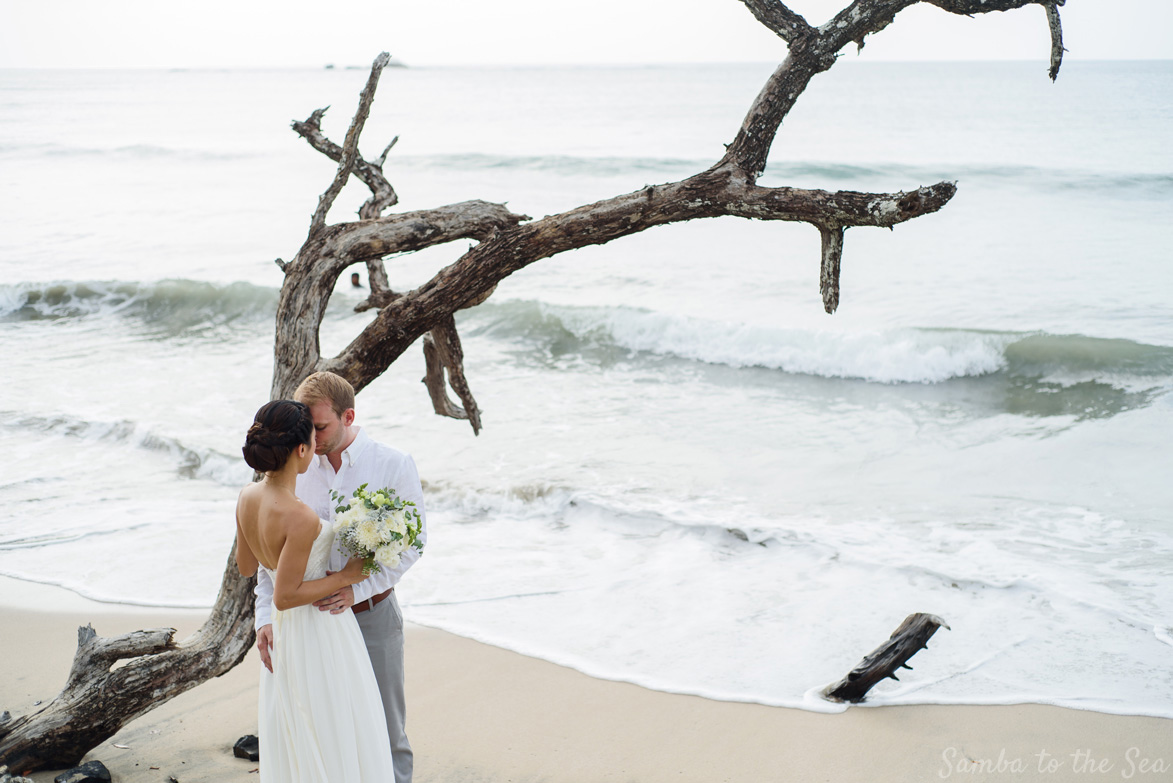 Bride and groom kissing on the beach after their wedding in Tamarindo, Costa Rica. Photographed by Kristen M. Brown, Samba to the Sea Photography.