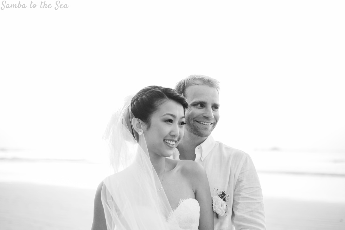 Bride and groom smiling on the beach in Tamarindo, Costa Rica. Photographed by Kristen M. Brown, Samba to the Sea Photography.