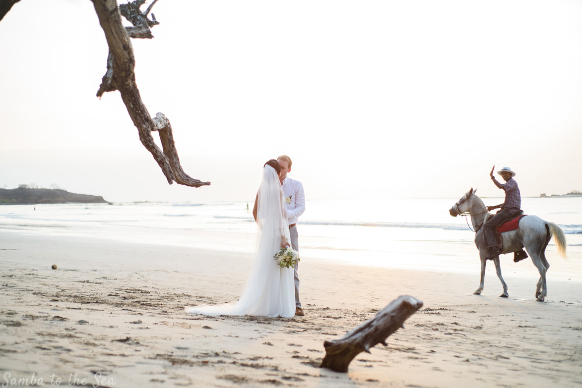 Caballero Cowboy passing behind bride and groom on the beach in Tamarindo, Costa Rica. Photographed by Kristen M. Brown, Samba to the Sea Photography.