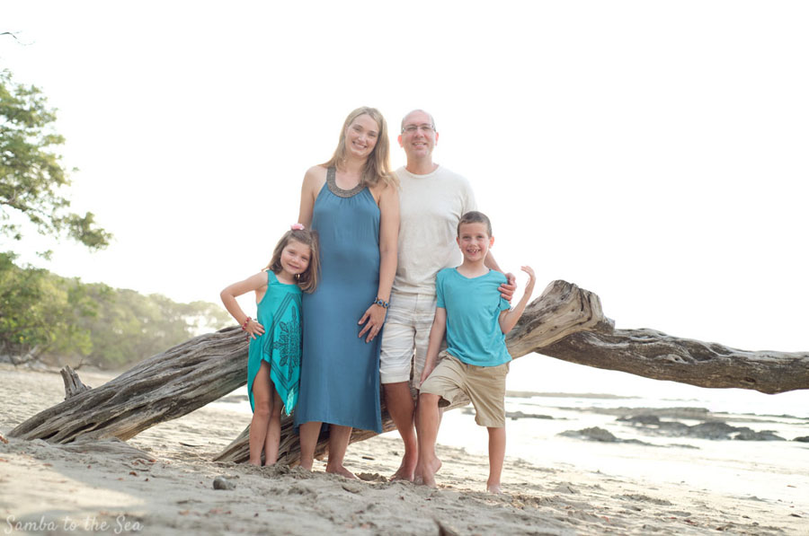 Family photo with a beautiful piece of driftwood in Tamarindo, Costa Rica. Photographed by Kristen M. Brown, Samba to the Sea Photography.