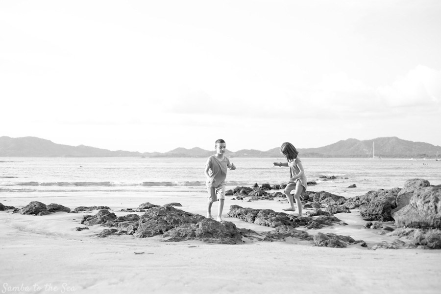Siblings playing on the rocks on the beach in Tamarindo, Costa Rica. Photographed by Kristen M. Brown, Samba to the Sea Photography.