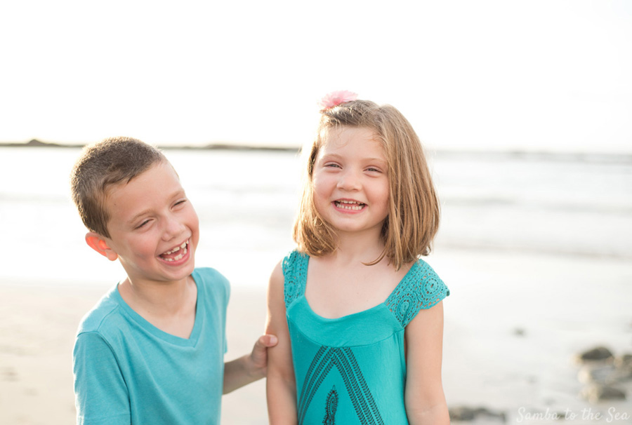 Siblings laughing during family photos in Tamarindo, Costa Rica. Photographed by Kristen M. Brown, Samba to the Sea Photography.