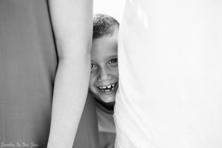 Young boy peeking through his parents with a huge smile on his face. Photographed by Kristen M. Brown, Samba to the Sea Photography.