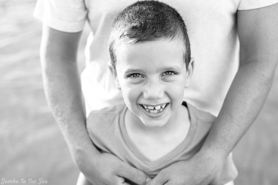 Young boy smiling during family portraits in Tamarindo, Costa Rica. Photographed by Kristen M. Brown, Samba to the Sea Photography.