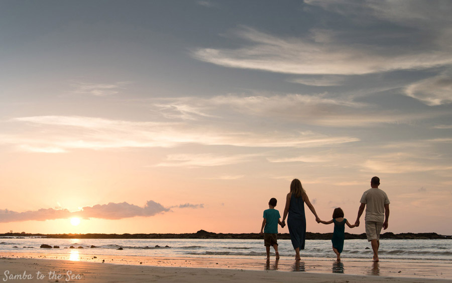 Family walking on the beach holding hands during sunset in Tamarindo, Costa Rica. Photographed by Kristen M. Brown, Samba to the Sea Photography.