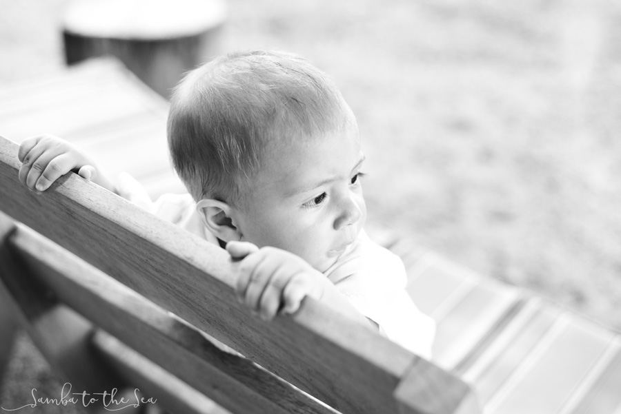 Black and white photo of baby boy looking into the distance at Pangas Beach Club in Tamarindo, Costa Rica. Photographed by Kristen M. Brown, Samba to the Sea Photography.