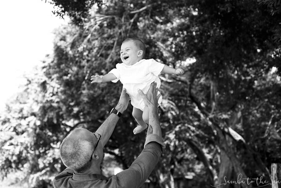Baby boy laughing as his dad throws him in the air in Tamarindo, Costa Rica. Photographed by Kristen M. Brown, Samba to the Sea Photography.