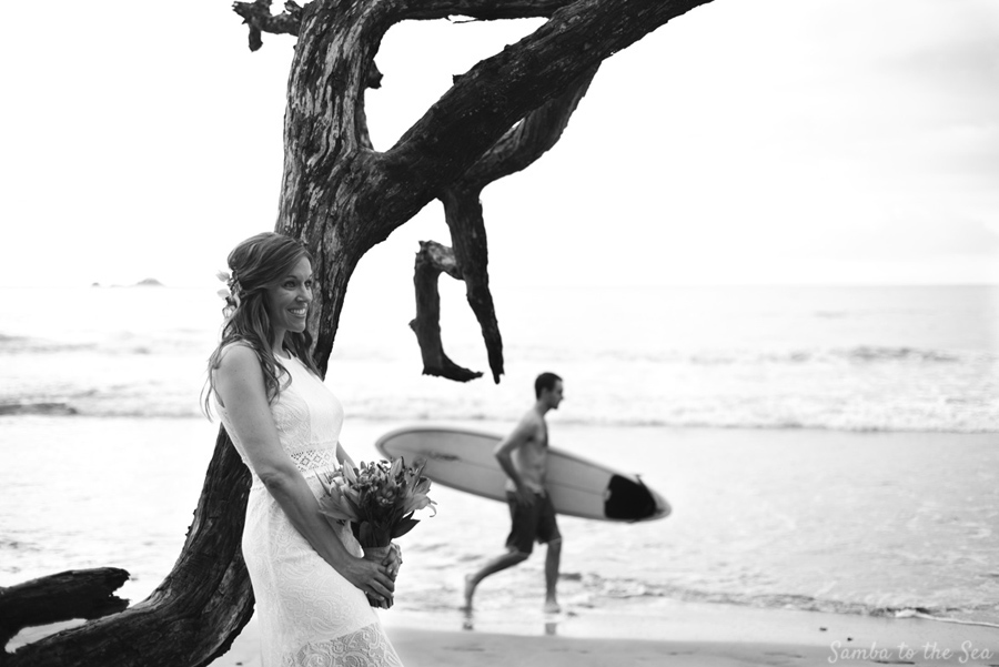 Bridal portrait on the beach in Tamarindo, Costa Rica with a surfer. Photographed by Kristen M. Brown, Samba to the Sea Photography.