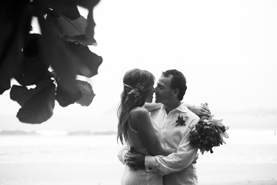 Bride and groom embracing in a plam tree grove after their elopement in Costa Rica. Photographed by Kristen M. Brown, Samba to the Sea Photography.