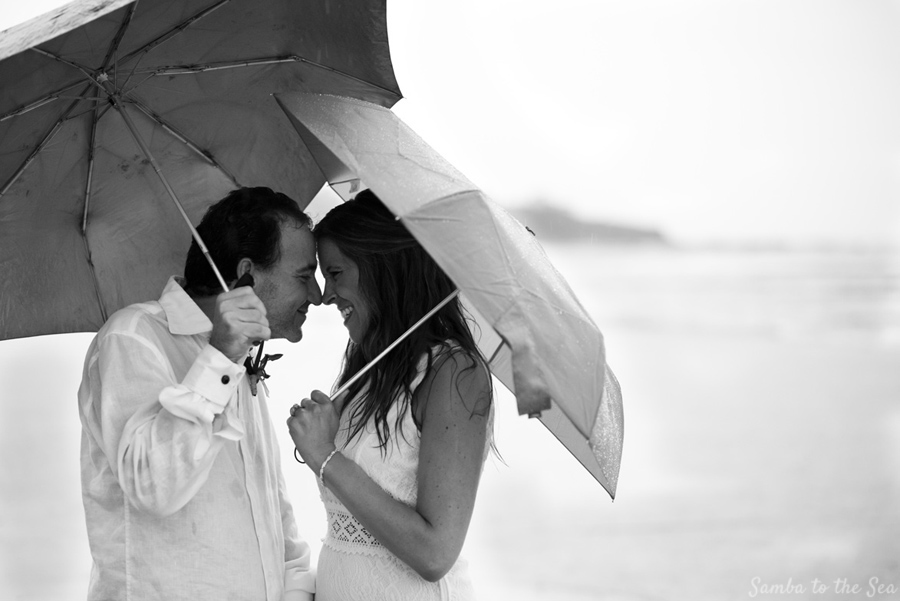Bride and groom nuzzling their foreheads in the rain. Photographed by Kristen M. Brown, Samba to the Sea Photography.