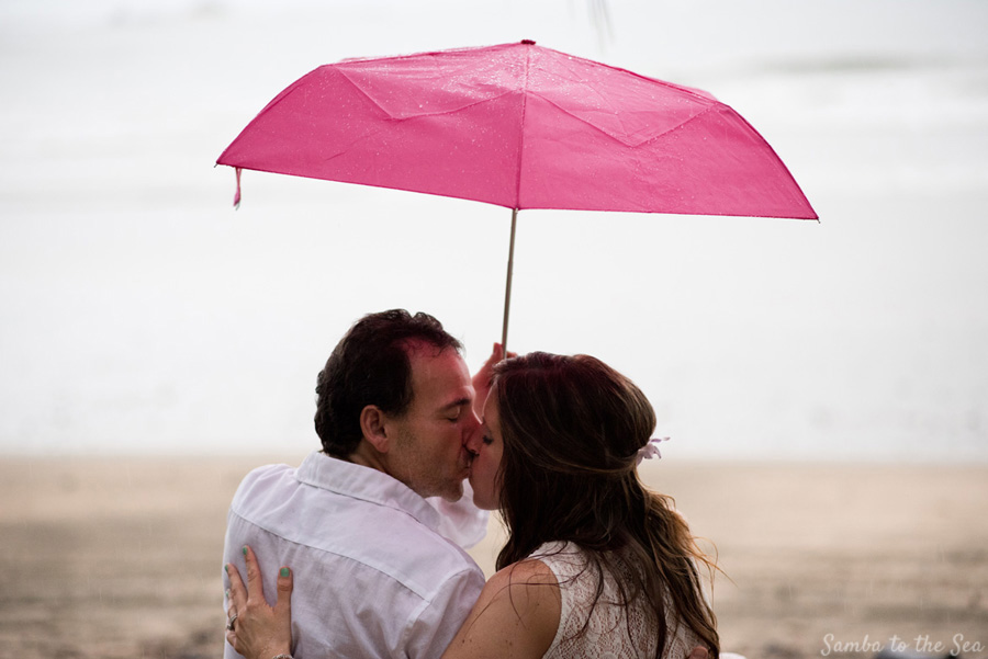 Bride and groom walking on the beach during a Costa Rican downpour. Photographed by Kristen M. Brown, Samba to the Sea Photography.