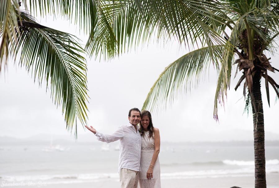 Bride and groom embracing the rain during their elopement in Costa Rica. Photographed by Kristen M. Brown, Samba to the Sea Photography.