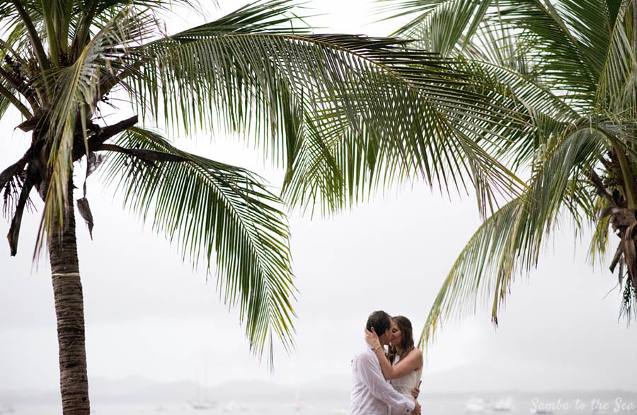 Couple romantically kissing under palm trees in Costa Rica. Photographed by Kristen M. Brown, Samba to the Sea Photography.