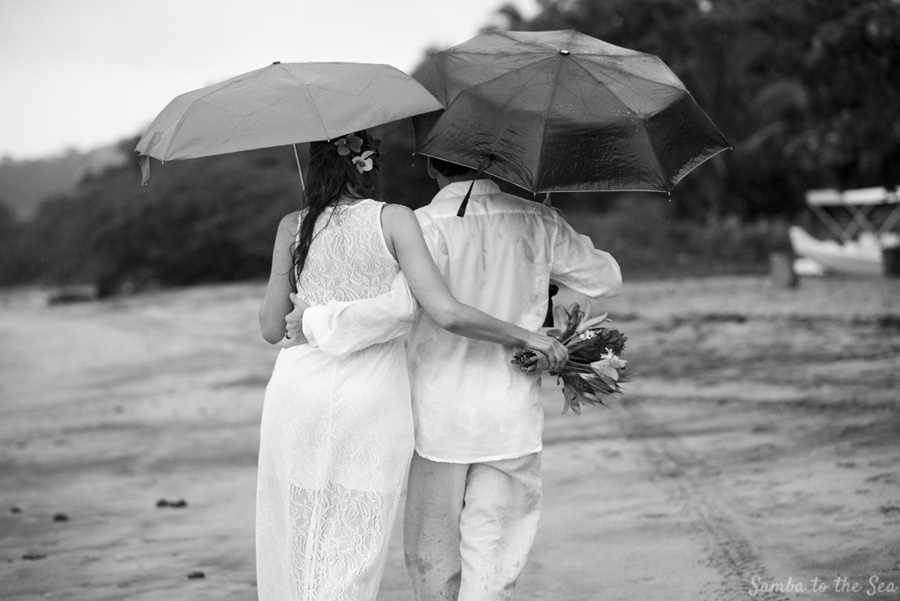 Bride and groom kissing under an umbrella in Costa Rica. Photographed by Kristen M. Brown, Samba to the Sea Photography.