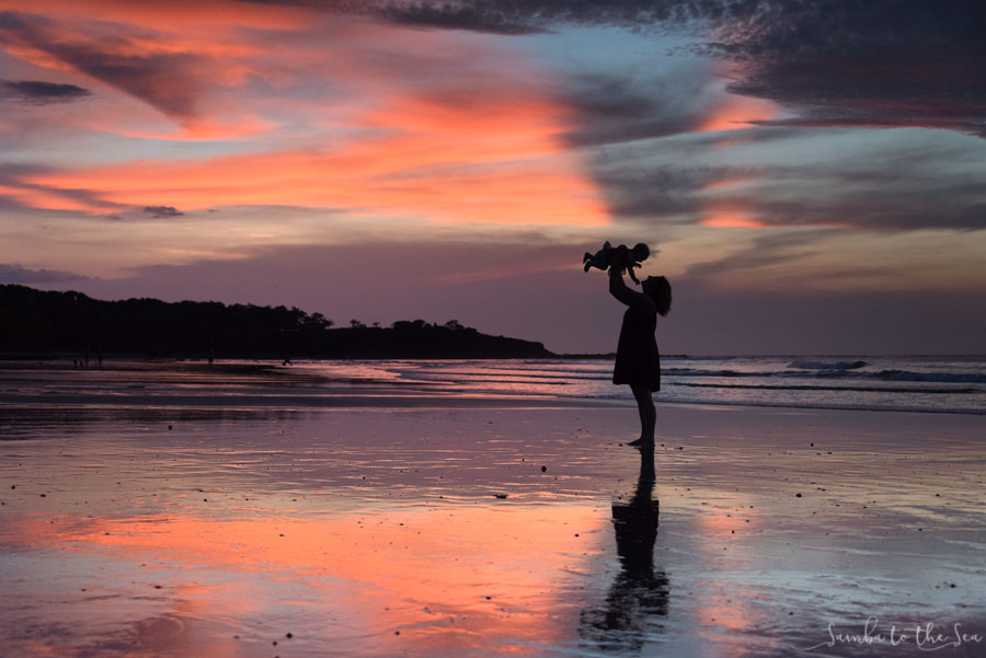 Stunning Costa Rican sunset in Tamarindo, Costa Rica with a silhouette of a mom holding her baby girl in the air. Photographed by Kristen M. Brown, Samba to the Sea Photography.