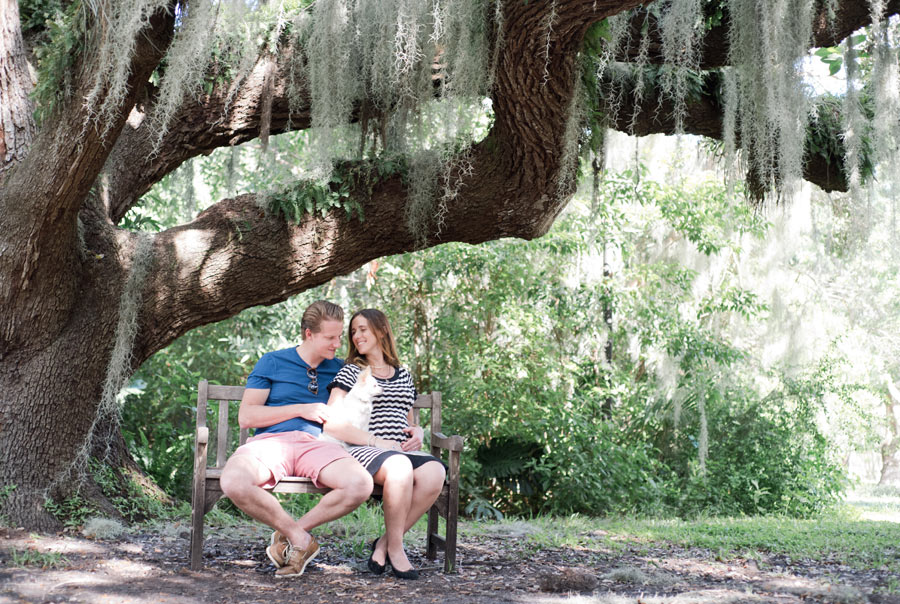Couple sitting on bench with their long hair Chihuahua at Barnacle Historic Park in Coconut Grove, Florida. Photographed by Savannah Maternity Photographer, Kristen M. Brown, Samba to the Sea Photography.